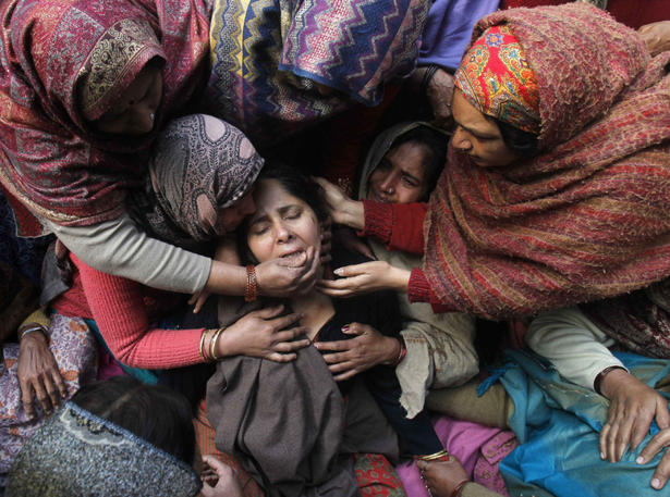 Unidentified women console the wife of Subhash Tomar, a policeman, during his funeral in New Delhi.
