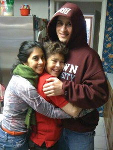 Sunil Tripathi, in his Brown University hoodie, gets a group hug in the family kitchen.